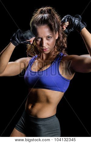 Portrait of confident boxer with fighting stance against black background