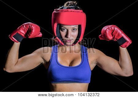 Portrait of female fighter with gloves and headgear against black background