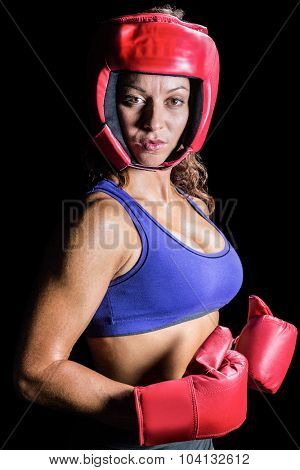 Portrait of pretty boxer with headgear and gloves against black background