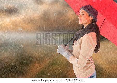 Smiling brunette holding red umbrella against country scene