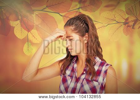 A pretty brunette with headache against autumn scene