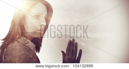Depressed businesswoman looking away against trees and mountain range against cloudy sky