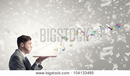 Young businessman with opened book in hands blowing on pages