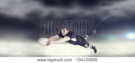 A rugby player scoring a try against spotlight