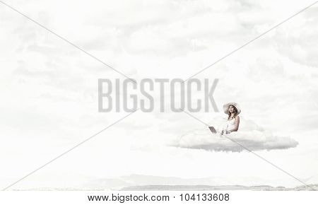 Young lady sitting on cloud with laptop on knees
