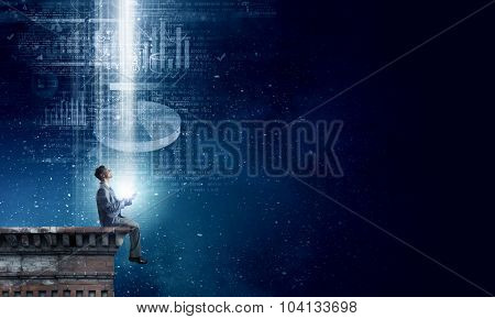 Young businessman sitting on building top with mobile phone in hand