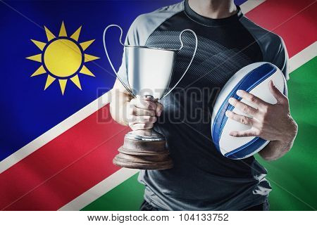 Midsection of successful rugby player holding trophy and ball against namibian flag on white background