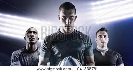 Thoughtful rugby player holding ball against spotlights