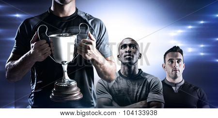 Victorious rugby player holding trophy against spotlight
