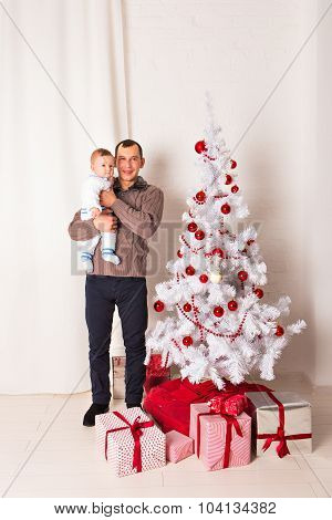 Father with a baby near Christmas tree.