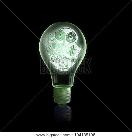 Glass light bulb with gears inside on black background