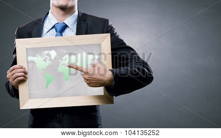 Unrecognizable businessman holding chalkboard with world map