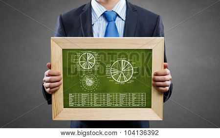 Unrecognizable businessman holding chalkboard with metal market graphs
