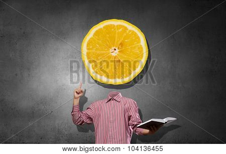 Headless man with book in hand anf lemon instead of head
