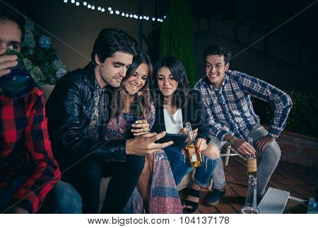 Happy friends laughing and looking smartphone in party