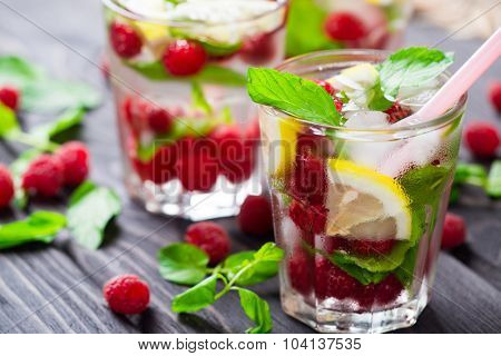 Lemonade with raspberry, lemon and mint in glass on rustic wooden background