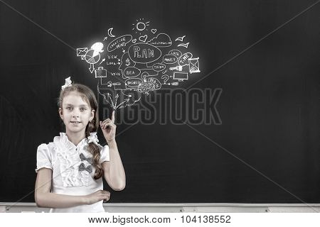 School girl pointing at chalk sketches on blackboard