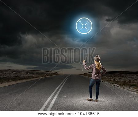 Young woman holding balloon with compass concept