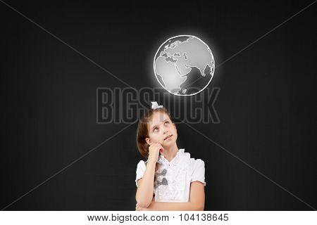 Cute thoughtful school girl and globe above her head