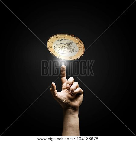 Human hand pointing with finger at euro coin