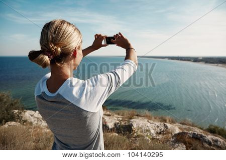 Woman Hiker Taking Photo With Smart Phone At Mountain Peak.