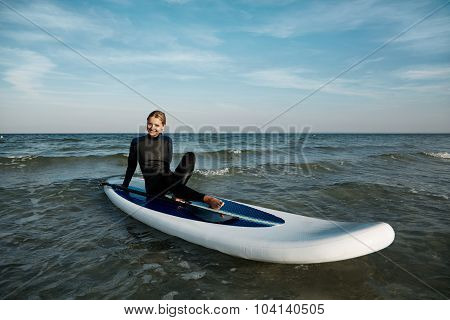 Beautiful Young Woman Surfing Lies On Stand Up Paddle Board At Exotic Vacation At Deep Blue Sea.