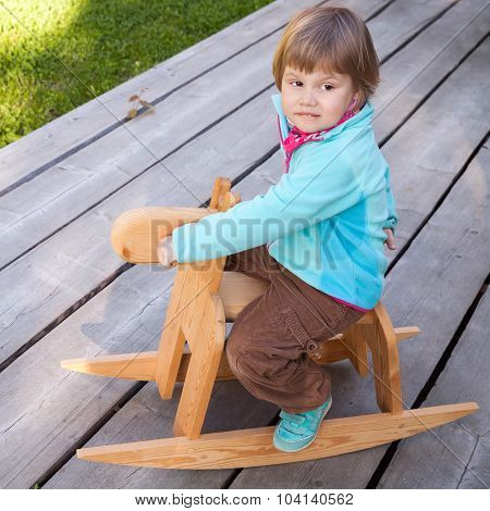 Baby Girl Riding Small Wooden Horse Toy