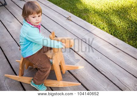 Cute Blond Baby Girl Riding Wooden Horse