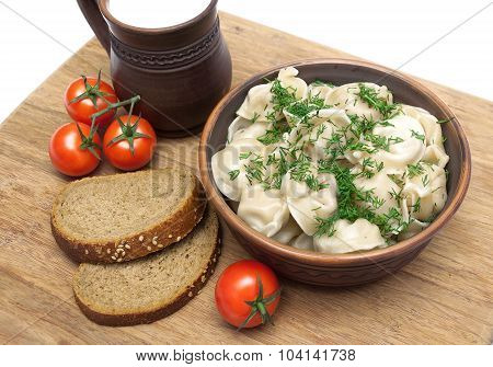 Russian Dumplings, Bread And Cherry Tomatoes On A Cutting Board