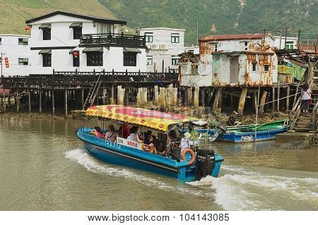 Tourists enjoy boat trip at the Tai O fishermen village with stilt houses in Hong Kong, China.