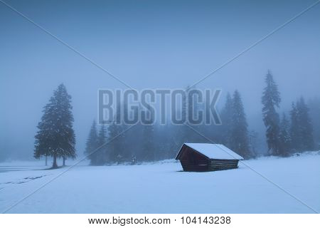 Old Wooden Hut In Foggy Winter Forest
