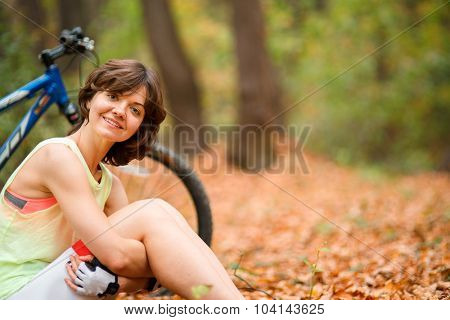 beautiful smiling woman sitting next to bike in park
