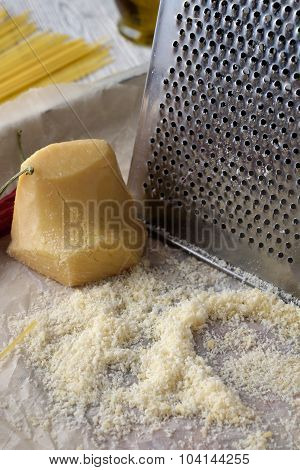 Grated Parmesan Cheese And Metal Grater On Wooden Table