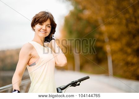 portrait of beautiful young woman with her bike outdoor