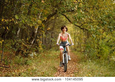 woman riding bike on path in park full of trees toned