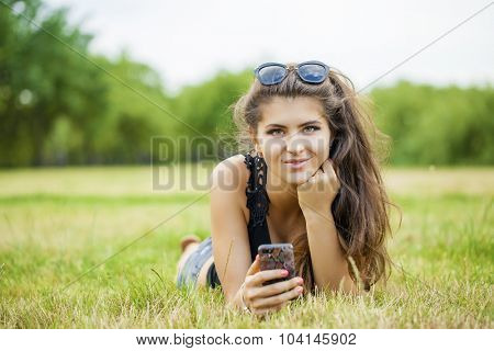 Portrait of beautiful caucasian smiling brunette young woman calling by phone, against summer green park