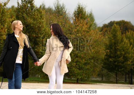 Two Young beautiful women walking in park, on yellow background autumn nature
