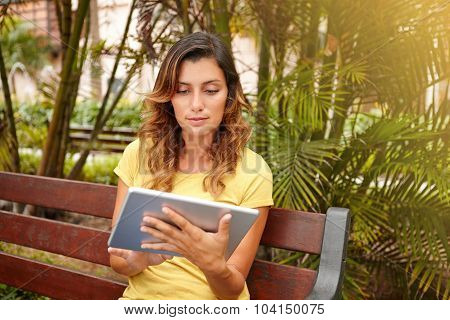 Young Woman Using Tablet While Sitting On Bench