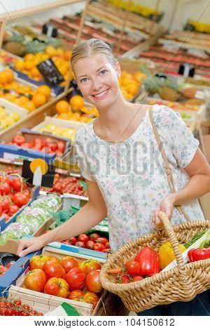 Filling her basket up with vegetables