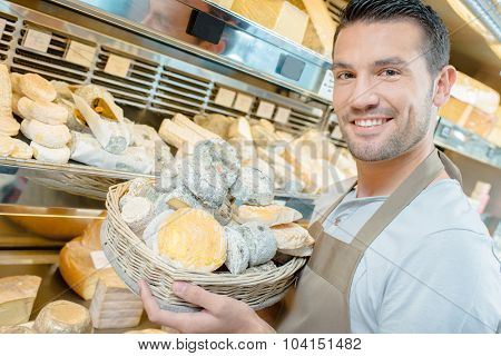Man displaying cheeses in basket