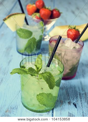 closeup of some glasses with different mojitos, such as regular mojito, melon mojito or strawberry mojito, on a rustic blue wooden table