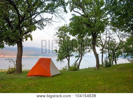 Orabge camping tent on a river shore in a morning light