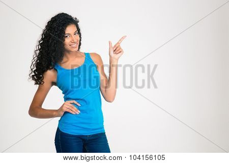 Portrait of a happy afro american woman pointing finger away isolated on a white background