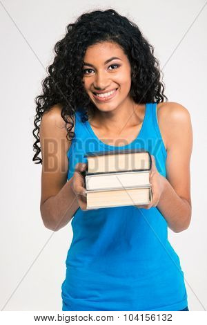 Portrait of a smiling afro american woman holding books isolated on a white background