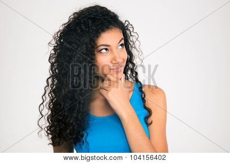 Portrait of a pensive afro american woman looking up at copyspace isolated on a white background