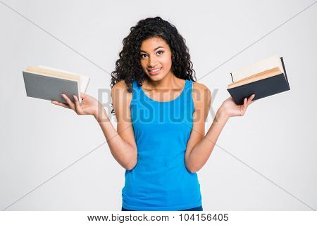Portrait of a smiling afro american woman holding two books isolated on a white background