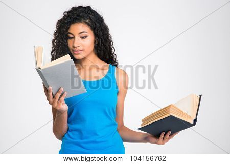 Portrait of a beautiful afro american woman holding two books isolated on a white background