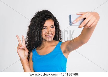 Portrait of a smiling afro american woman making selfie photo while showing two fingers sign isolated on a white background