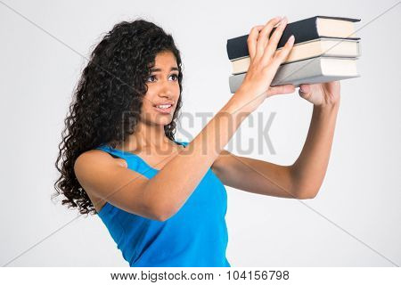 Portrait of a sad young woman looking on many books isolated on a white background