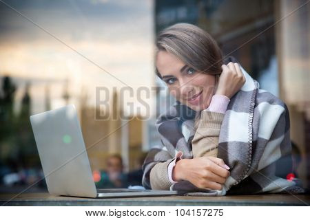 Portrait of a smiling girl sitting with laptop in cafe and looking at camera